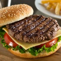 A delicious grilled Angus beef burger with cheese, lettuce, and tomato on a sesame seed bun.